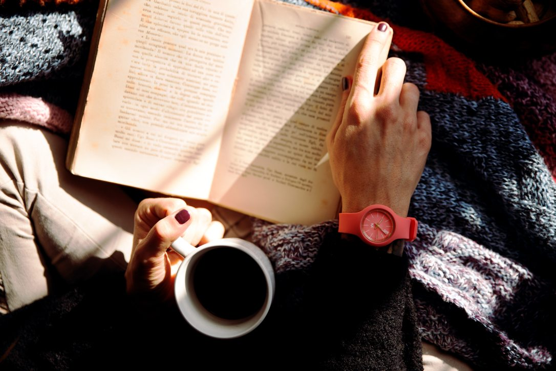 person-reading-book-and-holding-coffee-1550648
